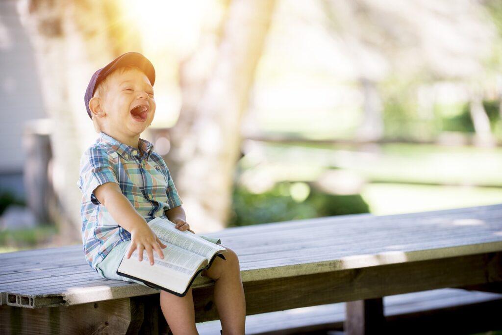 Bimbo che ride, seduto su una panchina