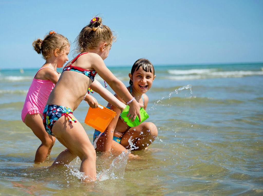 Bambini bimbi che giocano nel mare di Jesolo, in vacanza.