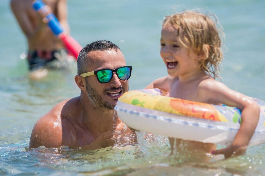 Bambina felice che gioca in mare col papà